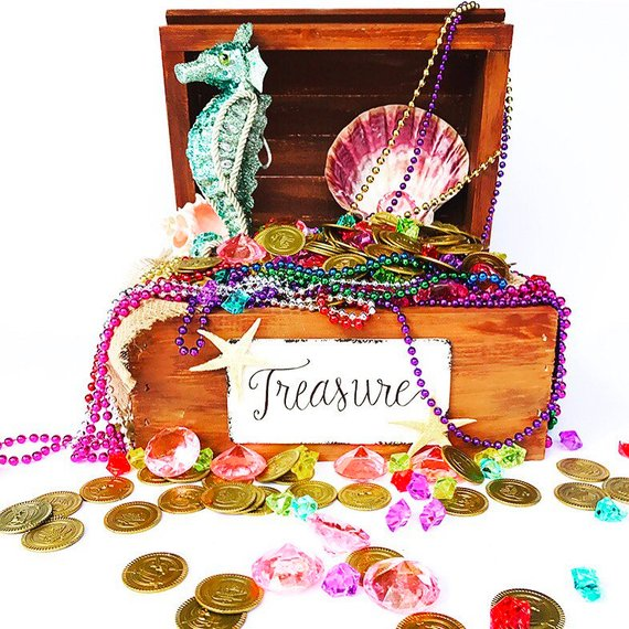 An open treasure chest rests against a white background. The word 'treasure' is scribed in cursive upon a white plaque set before it. The treasures within it consist of a blue seahorse, pink stones, purple stones, colorful necklaces and gold coins.